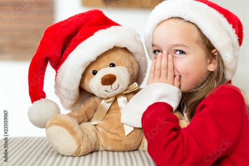 Cute young girl wearing santa hat whispering a secret to her teddy bear christmas present toy. Cheeky kid sharing secrets with teddy bear.