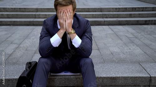 Obraz Desperate male sitting on ladder near building loosing all money on stock market - fototapety do salonu