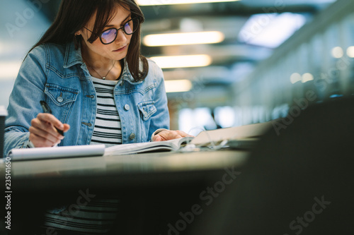 Fotografia  Female student reading a book and writing notes