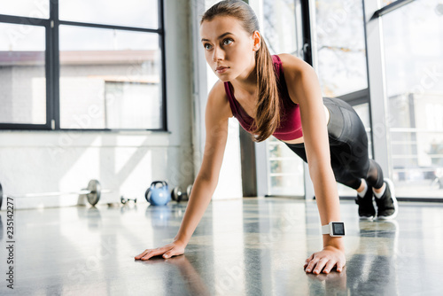 beautiful focused sportswoman doing push ups at fitness center - 235142277