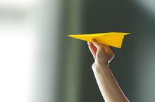 Hand Holding Paper Airplane