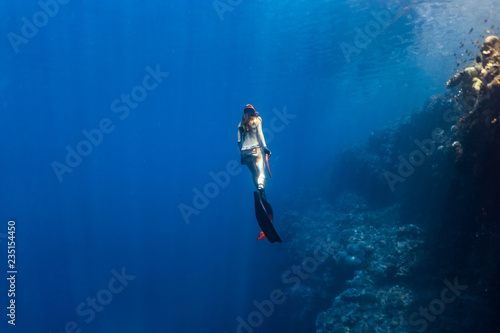Cadres-photo bureau Plongée Sexy free diver wearing bikini ascends to the surface from a deep breath hold dive