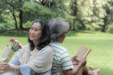 Retirement Couple, Sitting And Picnic On Green Lawn In Shady Park, With Flowers And Books, It Mages For A Happier Holiday.
