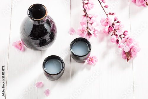 Top view of sake with flowers of blooming cherry