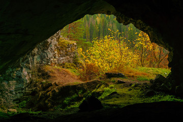 view from the dark natural cave to the bright autumn mountain landscape outside
