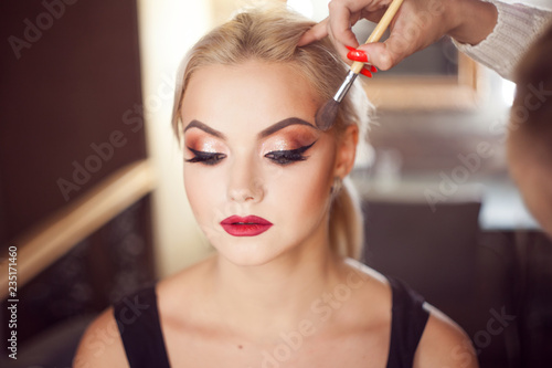Obraz Beautiful young blonde. Makeup artist makes a stylish makeup. - fototapety do salonu