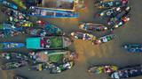 WIDOK Z LOTU PTAKA: Miejscowi ludzie kupują i sprzedają kolorowe produkty z drewnianych łodzi. - 235178672