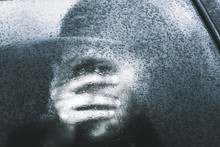 Person Closing Face By Hand In Glass With Glaze Ice