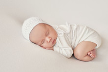 Cute Newborn Baby Girl Lies Swaddled In A White Blanket. Baby Goods Packaging Template. Closeup Portrait Of Newborn Baby With Smile On Face. Healthy And Medical Concept.