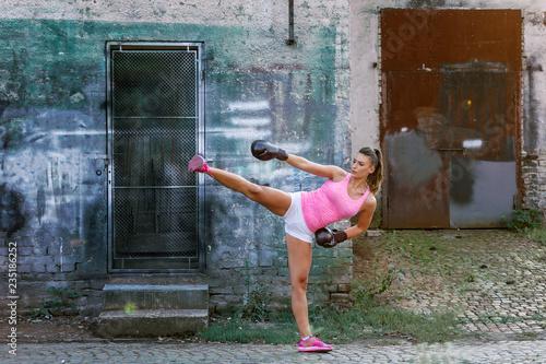 Kick boxer girl exercise on street Wallpaper Mural