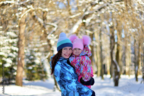Mother with a little daughter on a walk in the woods on a snowy winter day.