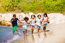 Happy Kids Running Together Along Sandy Beach