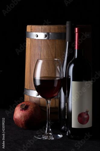 Fotografía  Still life with pomegranate wine on a black background