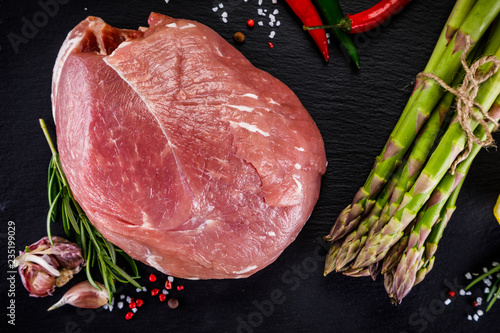 Fresh raw pork with vegetables on cutting board on wooden background