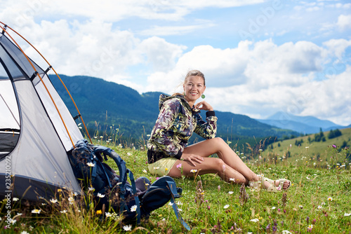 701f1c3c3f0 Beautiful woman tourist hiking mountain trail, sitting near tent and  backpack, smiling to the