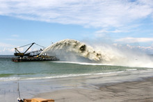 Work Dredger Dredging With Sand Washing On Beaches. Special Dredging Hose For Sand To Create New Land. Sand Washing On Sea Beaches. Dredging, Washing Out Sand On Beach During Construction Sea Terminal