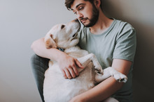 Pleasant Bearded Man Sitting In The Arm Chair While Holding His Dog