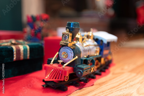 Toy Train under the Christmas Tree with presents in the background