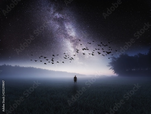 Spoed Foto op Canvas Grijze traf. Dreamy surreal landscape with starry night sky and man silhouette