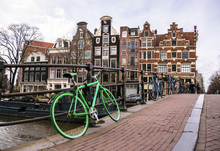 Amsterdam Canal Scene With Green Bike And Traditional Architecture