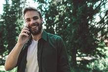 Communication During Interesting Travelling. Close Up Portrait Of Young Cheerful Man Talking By Mobile Phone While Standing On Green Trees Background