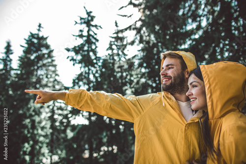 Enjoying journey in any weather. Close up portrait of cheerful man pointing on something far away to young woman while standing in yellow raincoats in green forest