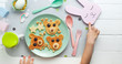 canvas print picture - Pink plate with pancakes and kids hands on white wooden background