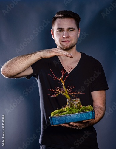 Young man holding japanese bonsai tree.