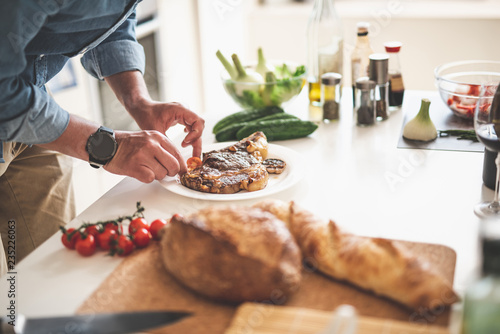 Close up of male hands holding slice of tomato near plate with grilled meat. Gentleman standing near white kitchen table