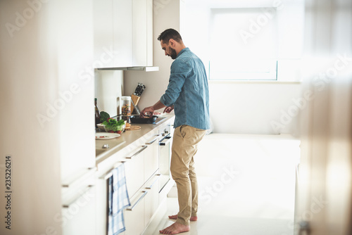 Side view full length portrait of handsome gentleman putting burger bun in frying pan