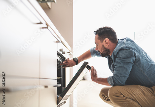 Side view portrait of handsome gentleman in denim shirt looking into oven while holding tongs. He is squatting on the floor
