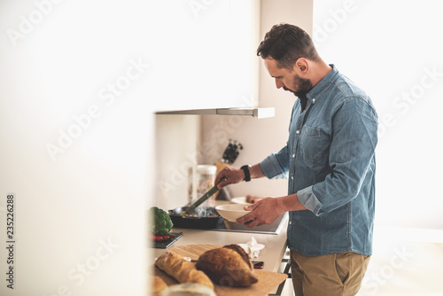 Side view portrait of handsome gentleman in denim shirt cooking dinner at home. Cutting board, bread and broccoli on table