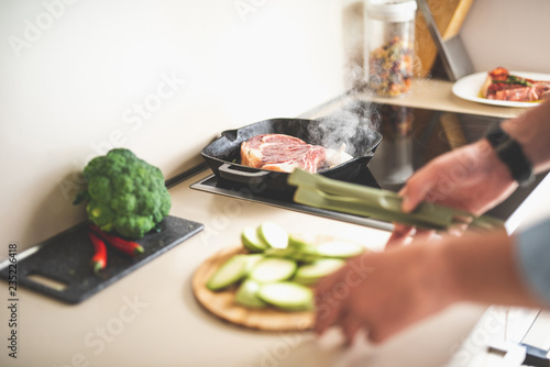 Close up of beef steak with garlic on frying pan. Blurred male hands holding kitchen tongs and cutting board with chopped zucchini