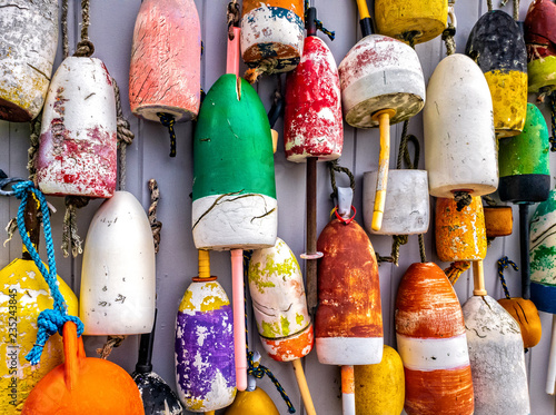 Fotografie, Tablou Colorful lobster buoys hang on the outside wall of a fishing shack, in Maine