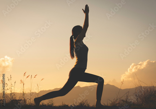 Spoed Foto op Canvas School de yoga silhouette woman practicing yoga on top of mountain
