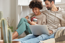 Image Of Interracial Lovely Couple In Love Rest At Home Interior, Satisfied With Communication And Gadgets, Drink Coffee, Hug Warmly, View Common Photos On Cell Phone, Pose In Modern Flat, Chat Online