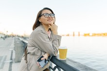 Outdoor Portrait Of Mature Smiling Woman In Glasses With Cup Of Coffee And Mobile Phone. Woman In The City On The Embankment Of The River.