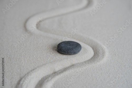 Photo sur Aluminium Zen pierres a sable Gray zen stones on the sand with wave drawings. Concept of harmony, balance and meditation, spa, massage, relax