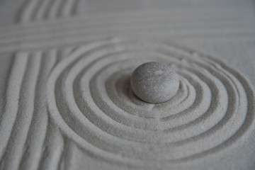 Fototapeta na wymiar Gray zen stones on the sand with wave drawings. Concept of harmony, balance and meditation, spa, massage, relax