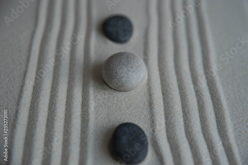 Cadres-photo bureau Zen pierres a sable Gray zen stones on the sand with wave drawings. Concept of harmony, balance and meditation, spa, massage, relax