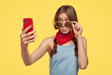 Isolated Shot Of Fashionable Teenage Girl Pouts Lips, Looks Through Trendy Sunglasses, Wears Red Bandana Near Neck, Holds Smart Phone, Makes Selfie Portrait, Enjoys Spare Time, Stands Over Yellow Wall