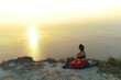 Beautiful view of woman doing yoga meditation on the mountain with sea view at sunset.