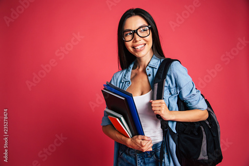 Carta da parati Happy and excited cute young student girl portrait in glasses with backpack isol