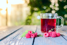 Tea With Ripe Raspberries And Green Fresh Brewed Leaves Healthy For Health On A Wooden Table