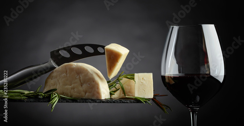 Sheep cheese with rosemary and glass of red wine.