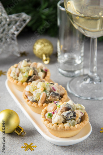 Russian salad with meat in tartlet. With potatoes, egg, cucumber, onion, mushrooms and mayonnaise. Olivier for new year table, Christmas appetizer