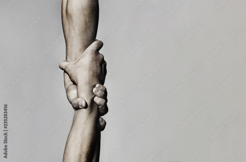 Fototapeta Helping hand concept and international day of peace, support. Helping hand outstretched, isolated arm, salvation. Close up help hand. Two hands, helping arm of a friend, teamwork. Black and white