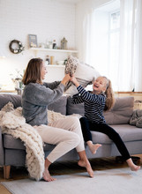 Mother And Child Having Fun In Pillow Fight On Sofa Bed In Bedroom. Happy Family Spending Time Together At Home.