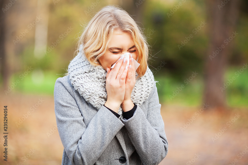 Fototapety, obrazy: Young woman blowing her nose on the park. Woman portrait outdoor sneezing because cold and flu