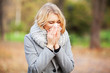 Young woman blowing her nose on the park. Woman portrait outdoor sneezing because cold and flu